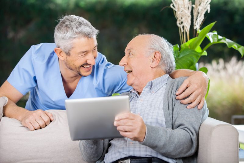 Laughing,Male,Caretaker,And,Senior,Man,Using,Tablet,Computer,At